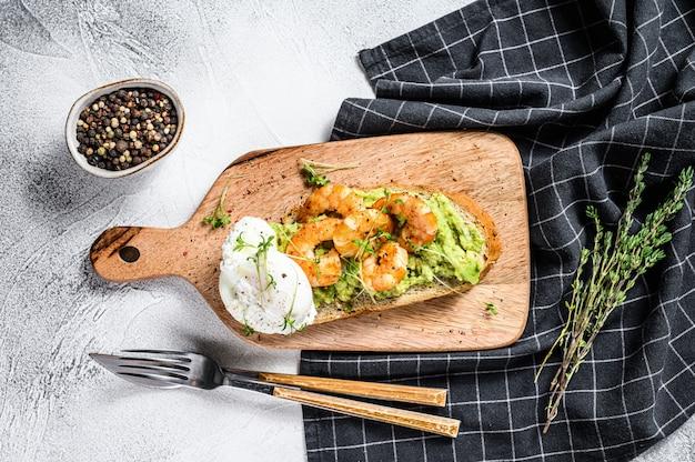 Бутерброд с хлебом, авокадо, креветками, креветками и яйцом всмятку. вид сверху