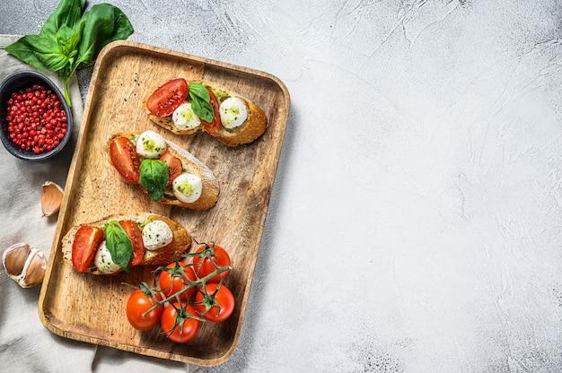 トマト、モッツァレラチーズ、バジルのサンドイッチ。イタリアの前菜、前菜。上面図。コピースペース
