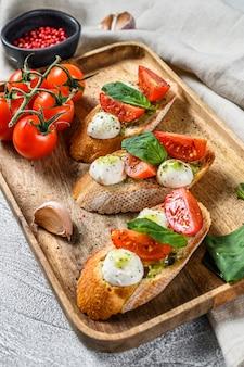 トマト、モッツァレラチーズ、バジルのサンドイッチ。イタリアの前菜、前菜。上面図