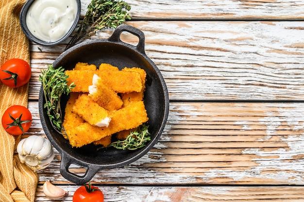 Хрустящие рыбные палочки с сухарями подаются с соусом тар-тар в сковороде на белом столе.