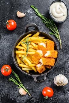 Рыба и чипсы с соусом тар-тар на черном столе.