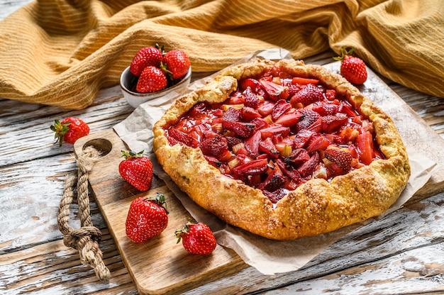 テーブルの上に焼きたてのイチゴとルバーブのパイ