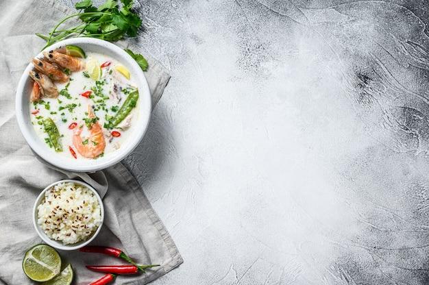 自家製トムカーガイ。ボウルにココナッツミルクスープ。タイ料理。灰色の背景。上面図。コピースペース