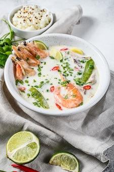 トム・カ・ガイ。鶏肉とエビのスパイシーなクリーミーなココナッツスープ。タイ料理。灰色の背景。上面図。
