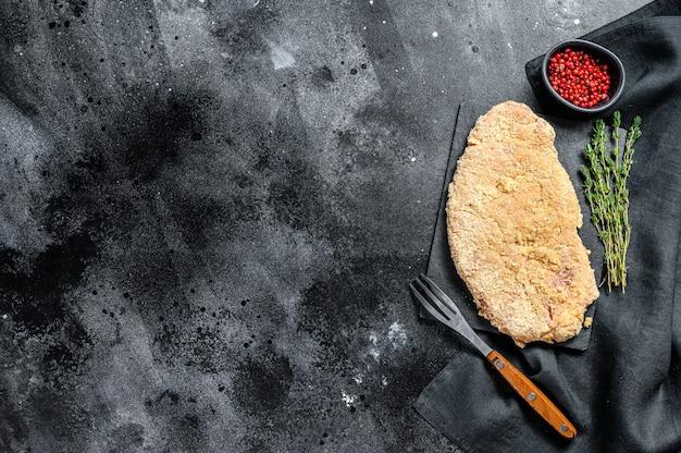 Сырой шницель по-венски, стейк в панировке, готовый к приготовлению.