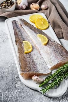 新鮮な生メルルーサ魚の切り身とレモンスライス