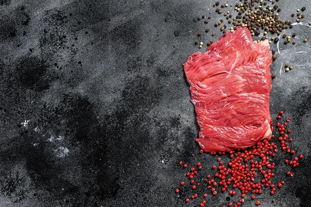 Сырой стейк на бочке с черным и розовым перцем.