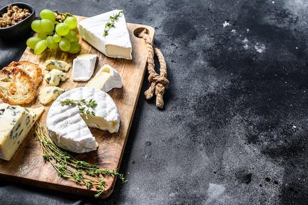 Сырная доска с французским камамбером, бри и голубым сыром, виноградом и грецкими орехами.