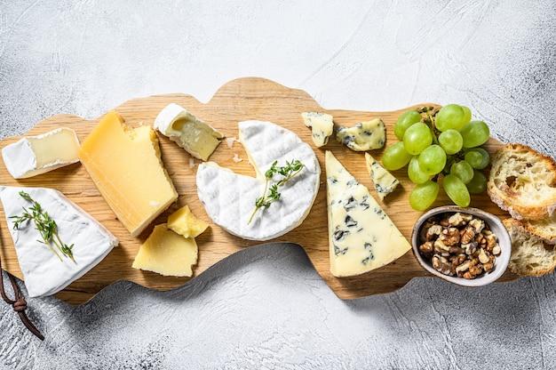 Сырная доска с французским камамбером, бри, пармезаном и голубым сыром, виноградом и грецкими орехами