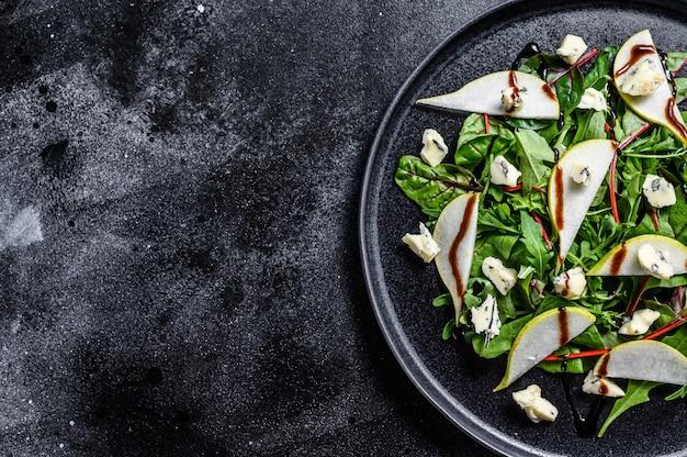 Салат с грушей, голубым сыром, рукколой и орехами на тарелке.