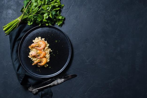 黒の皿にエビのイタリアンリゾット、コリアンダーの束。
