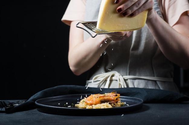 シェフは黒い皿の上にエビとイタリアのリゾットにパルメザンチーズをこする。