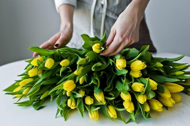 女の子の花屋はテーブルの上に黄色のチューリップを置きます。