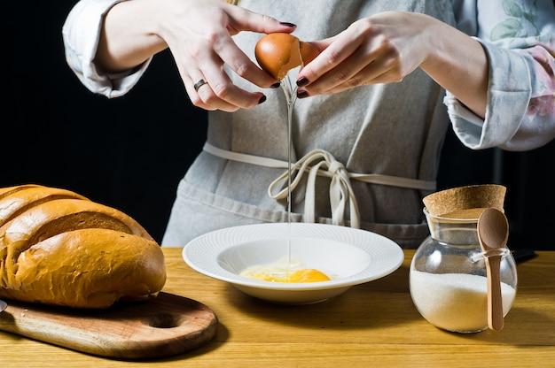 シェフが皿の上に鶏の卵を割る。フレンチトーストを調理するという概念。