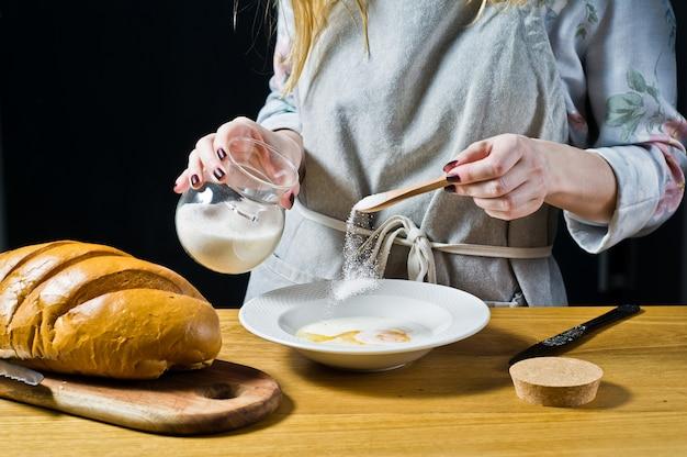 シェフは皿に砂糖を注ぐ。フレンチトーストを調理するという概念。