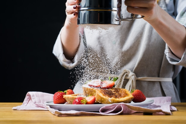 シェフがフレンチトーストに粉砂糖をふりかけます。