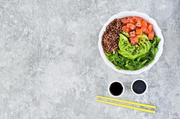 ポケ丼。材料:サーモン、アボカド、玄米、藻類。