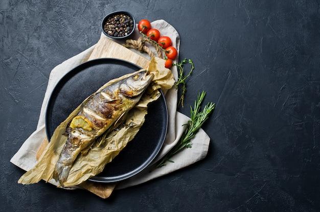Запеченный сибас на крафт-бумаги в черной тарелке.