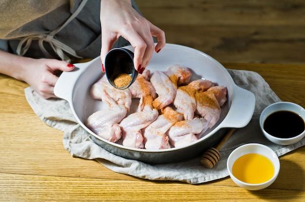 В руки шеф-повара приправляют пряностями сырые куриные крылышки.