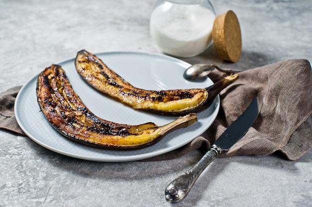 Жареные бананы с медом на серой тарелке.