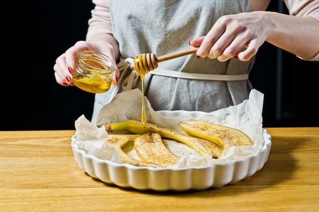 Шеф-повар наливает медовые ломтики бананов в форму для выпечки. готовим жареные бананы.