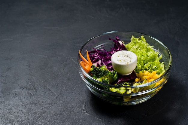 サラダボウル、健康的なベジタリアン料理。ブロッコリー、コーン、ニンジン、クスクス、レタス、キャベツ、ソース
