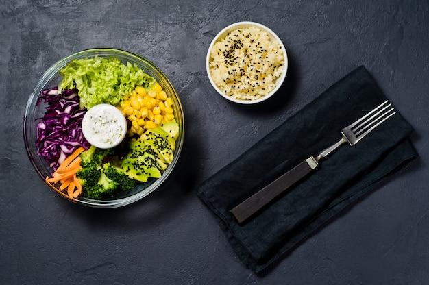 サラダボウル、健康的でバランスの取れた食べ物。ブロッコリー、コーン、ニンジン、クスクス、レタス、キャベツ、ソース