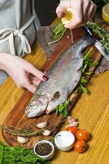 シェフは生のマスにパセリとディルを詰めた。材料ローズマリー、レモン、トマト、ニンニク、塩、コショウ。