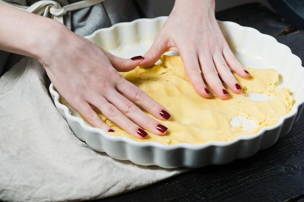 シェフはベーキング皿に生地をロールアウトして調理