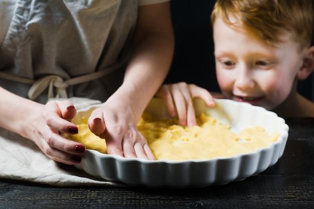 子供は母親がケーキを調理するのを助けます。