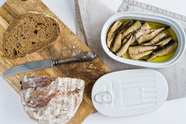 油、陶磁器の瓶、黒のパンと木製のまな板でスモークスプラットのサンドイッチ。