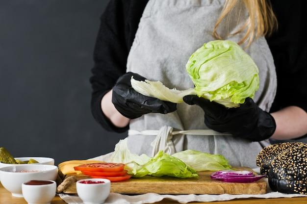 シェフはレタスを引きます。黒バーガーを調理するという概念。自家製ハンバーグレシピ。
