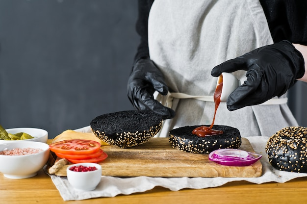 シェフはチーズバーガーを作っています。黒バーガーを調理するという概念。自家製ハンバーグレシピ。キッチン、サイドビュー、テキスト用のスペース。