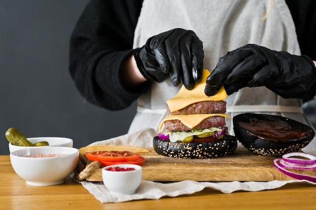 シェフは巨大なバーガーを用意しています。黒いチーズバーガーを調理することの概念。自家製ハンバーグレシピ。