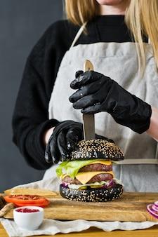 シェフはバーガーにナイフを刺します。黒いチーズバーガーを調理することの概念。自家製ハンバーグレシピ。