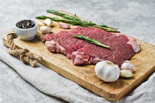 Сырой говяжий стейк на деревянной разделочной доске