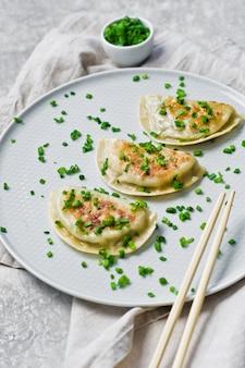 Домашние корейские пельмени, палочки для еды, свежий зеленый лук.