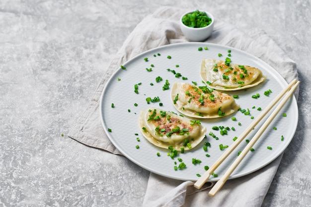 Китайские пельмени, палочки для еды, свежий зеленый лук.