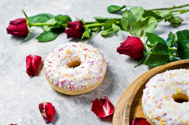 赤いバラで飾られた振りかけると白いドーナツ。