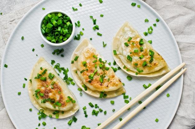 Корейские жареные пельмени, палочки для еды, свежий зеленый лук.