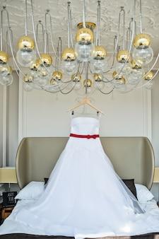 ホテルの部屋のシャンデリアに掛かっている花嫁の白いウェディングドレス