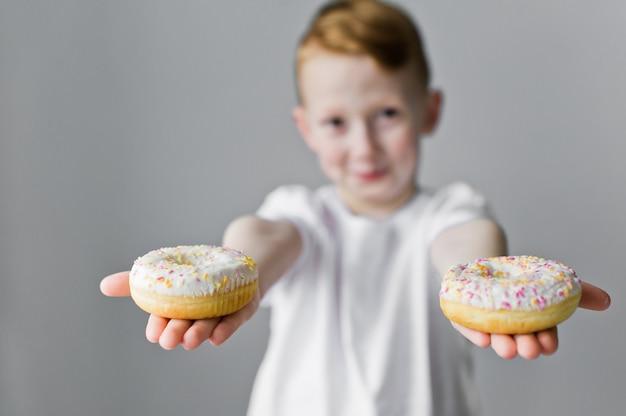 彼の手に白いドーナツと微笑む少年。