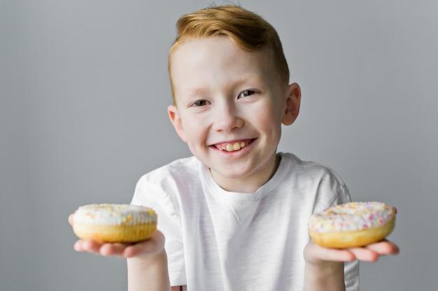 灰色の背景に対して白いドーナツと子少年。