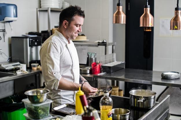 シェフはレストランのキッチンでフランベを作っています
