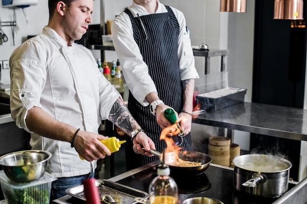 Шеф-повар готовит фламбе на кухне ресторана