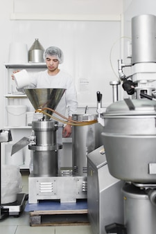 仕事は工業用粉砕機でココナッツチップを眠る-プレス。ココナッツオイル、ペーストの製造。