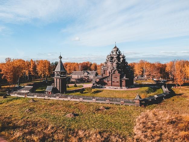 秋の森の古い木造の教会マナー神学者の空撮。ロシア、サンクトペテルブルク。