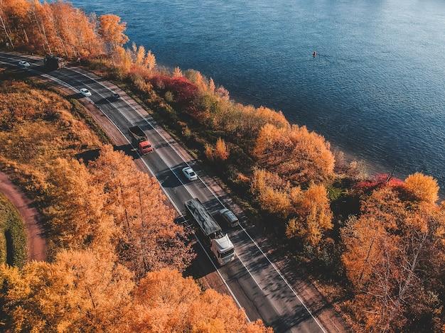 森の朝の光の空撮。カラフルな木々と青い湖の上から、曲がりくねった道。ロシア、サンクトペテルブルク