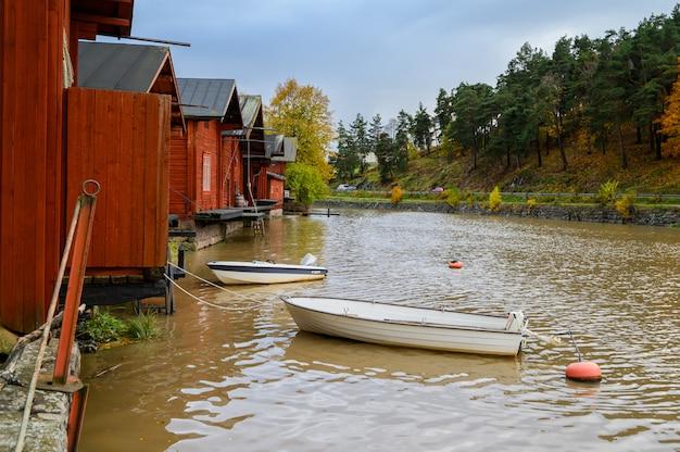 赤い家と納屋のある花崗岩の堤防。白いビルの船はブイに縛られています。