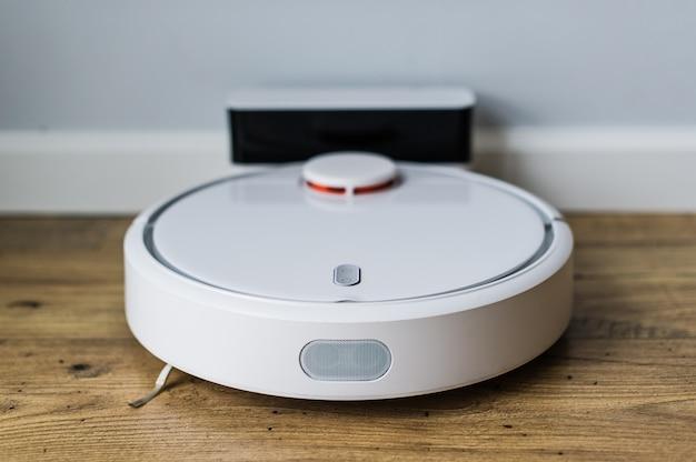 木製の床の上のロボット掃除機。上からの眺め。スマートホームのコンセプトです。自動クリーニング